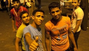 Young men pose for a photograph at Tahrir Square after the end of voting in the presidential election in Cairo